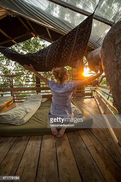 Young woman on tree house enjoying freedom-Sunset