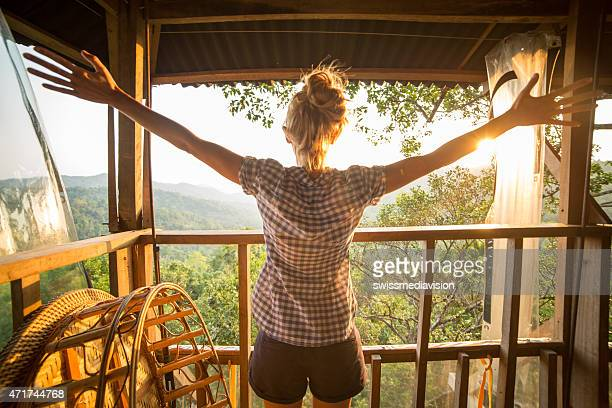 Young woman on tree house enjoying nature and freedom