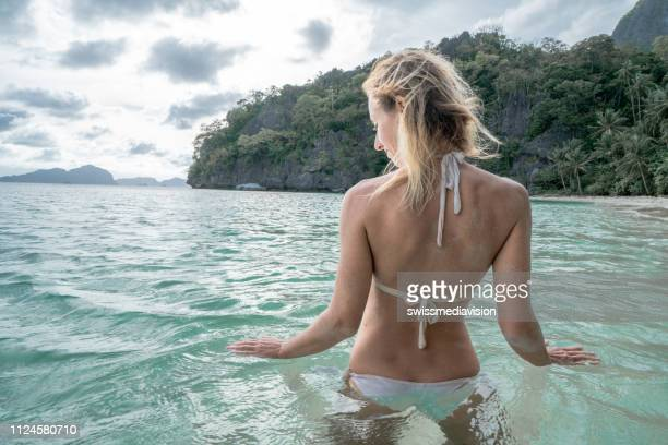 Young woman on tropical beach enjoys bathing in the sea