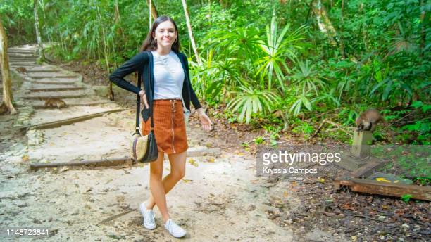 young woman on tropical rainforest trail with coatis - coati stock pictures, royalty-free photos & images