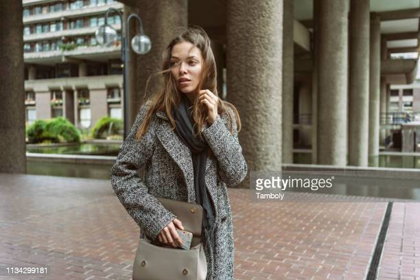 young woman on walkway of office building, london, uk - coat stock pictures, royalty-free photos & images