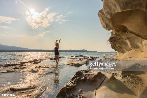 Mujer joven en la playa de desierto gritando hacia fuera con los brazos extendidos