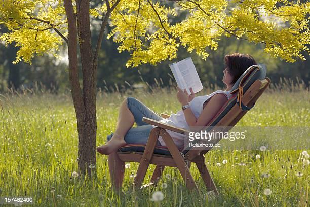 Jeune femme sur la terrasse en bois, chaise de lecture livre sous arbre