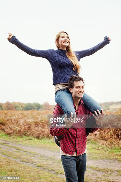 young woman on young mans shoulders. - carrying a person on shoulders stock photos and pictures