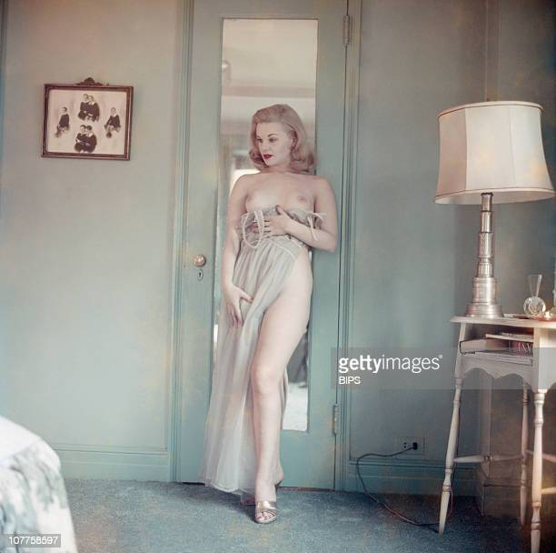 A young woman only partially conceals her nudity behind a nightgown circa 1955