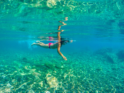 Young woman open arms and swimming freely 695502152