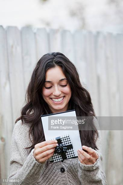 Young Woman Opening a Card and Gift.