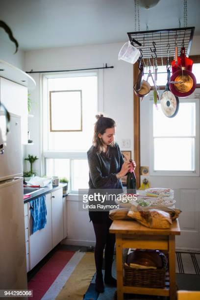 Young woman opening a champagne bottle in the kitchen