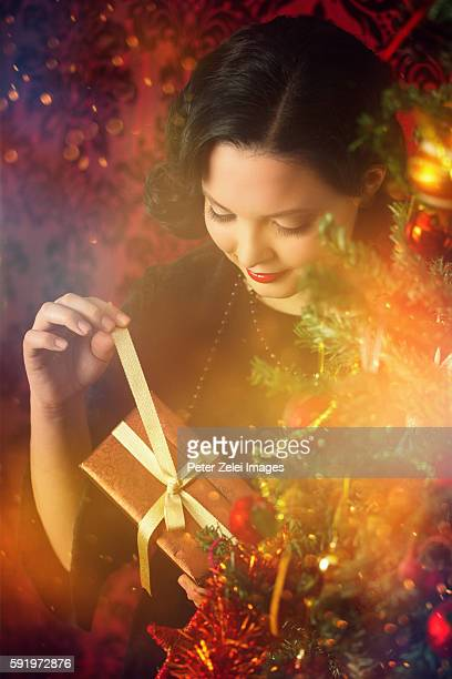 Young woman opening a christmas present