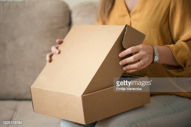 young woman opening a package - open blouse - fotografias e filmes do acervo
