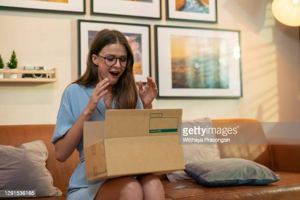 young woman opening a package - recevoir photos et images de collection