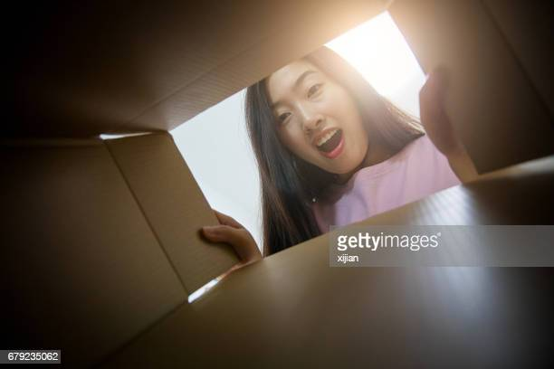 Young woman opening a parcel