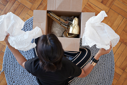 Young woman opening box with lamp at home - gettyimageskorea