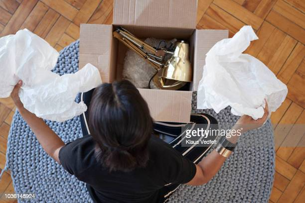 young woman opening box with lamp at home - onlinebanking stock-fotos und bilder