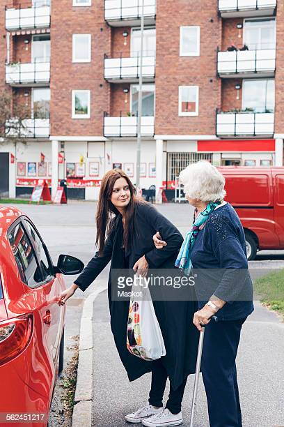 Young woman opening car door for grandmother on city street