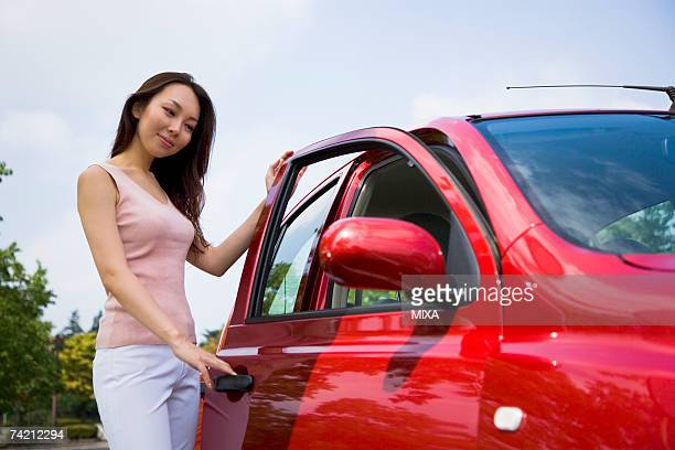 Young woman opening car door