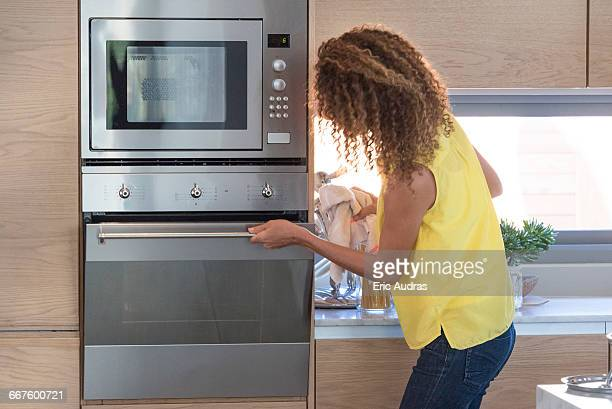Young woman opening door of an oven