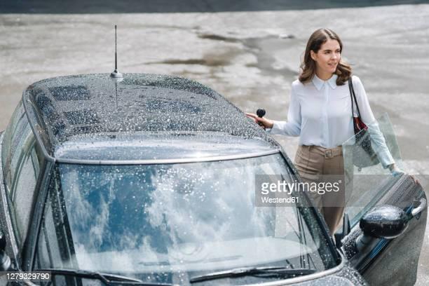 young woman opening door of car while standing at parking lot - entrando fotografías e imágenes de stock