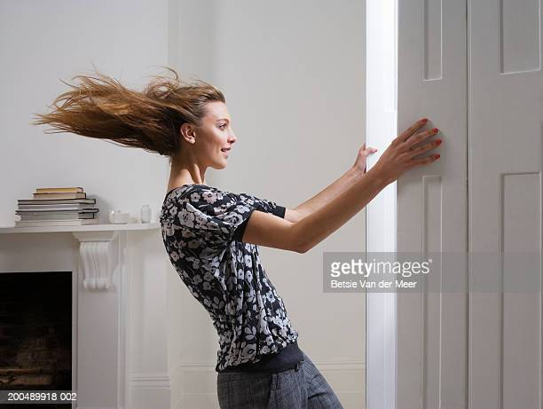 Young woman opening doors, hair blowing in strong gust of wind