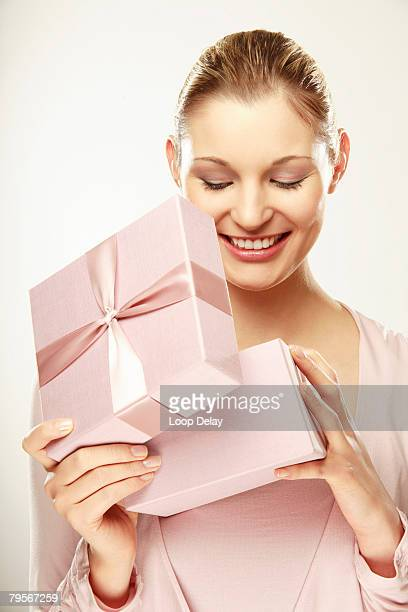 Young woman opening gift box, smiling, close-up