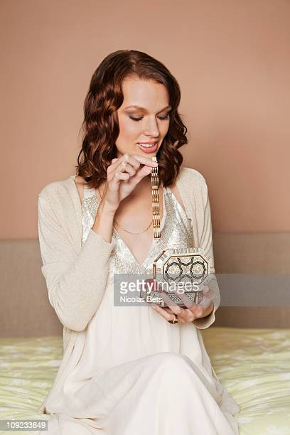 Young woman opening jewelry box