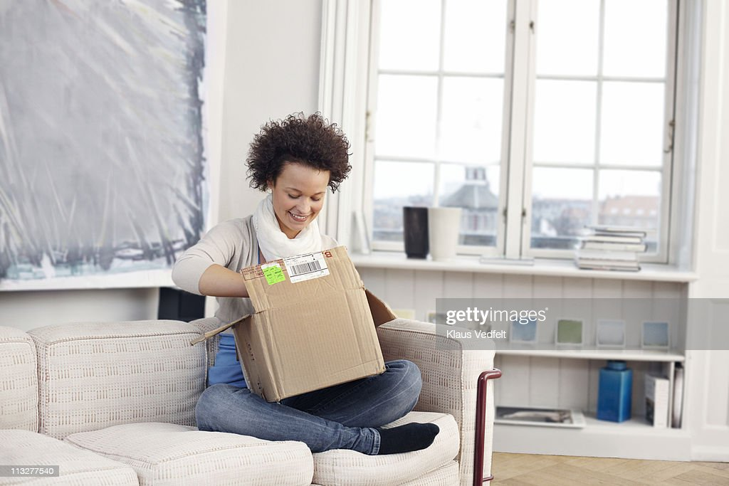 Young woman opening package : Stock Photo