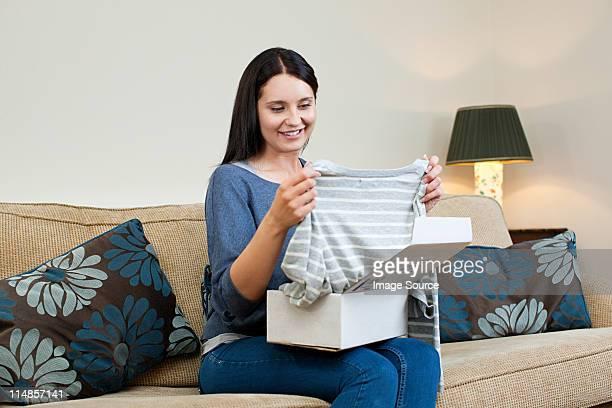 オープン予定の小包の若い女性