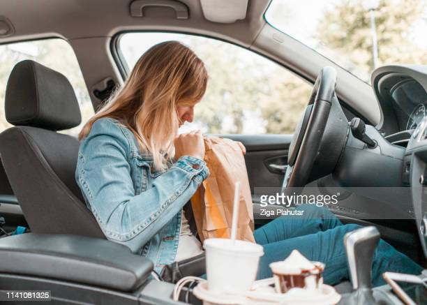 young woman opening take out food bag in a car - unhealthy living stock pictures, royalty-free photos & images