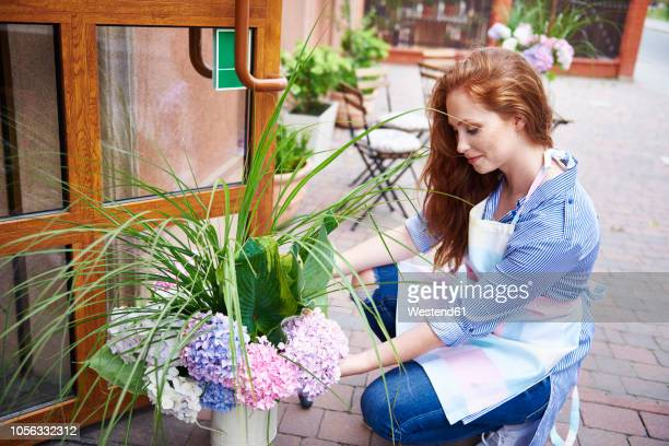 Young woman opening the door of a shop with flowers