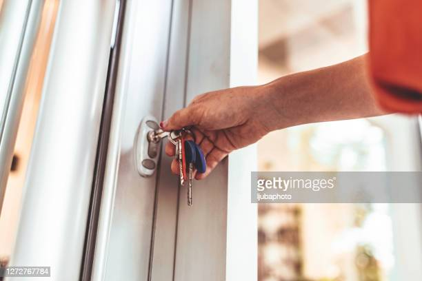 giovane donna che apre la porta d'ingresso del suo condominio - lucchetto foto e immagini stock