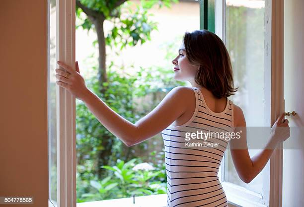young woman opening window to the garden - non urban scene stock pictures, royalty-free photos & images