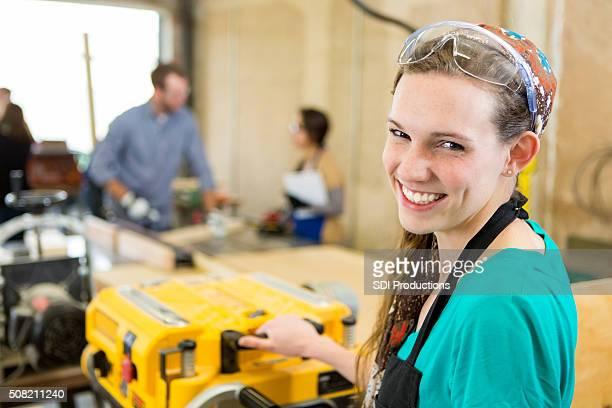 Junge Frau verkehrt der Maschine in der Werkstatt