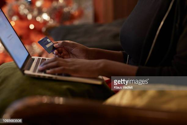 young woman ordering christmas gifts online - onlinebanking stock-fotos und bilder