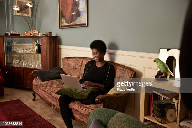 young woman ordering christmas gifts online - legs crossed at knee stock pictures, royalty-free photos & images