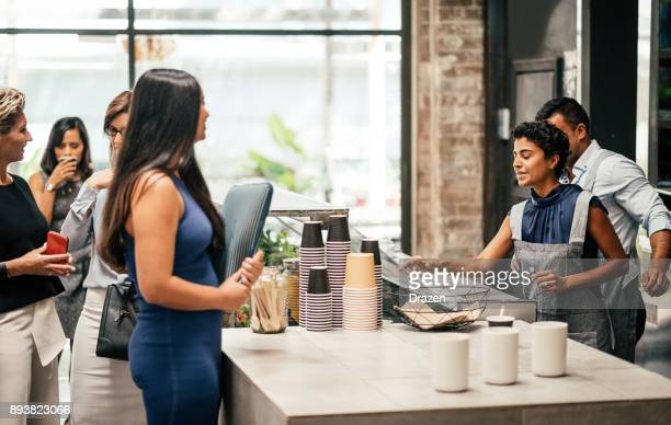 Young woman ordering coffee in bar during the coffee break at work