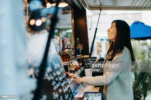 young woman ordering food and drinks from food truck - food truck fotografías e imágenes de stock