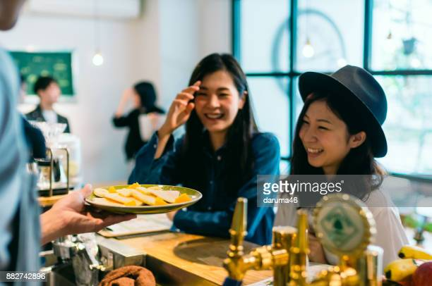 2 young woman ordering food at cafe