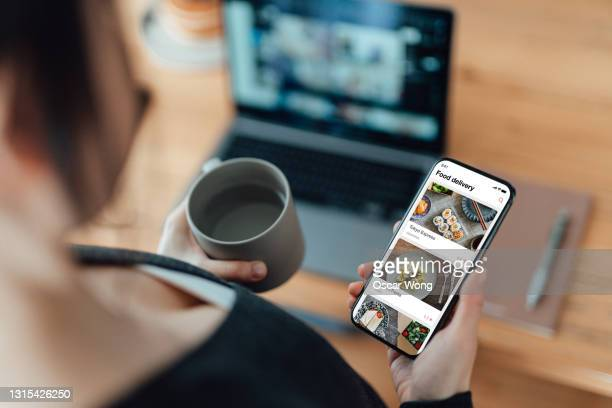 young woman ordering food online using mobile app on smartphone at work - computer equipment stock pictures, royalty-free photos & images