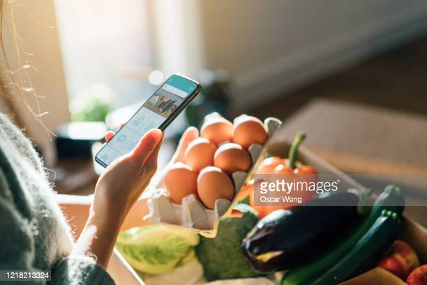 young woman ordering groceries online with smartphone - merchandise stock pictures, royalty-free photos & images