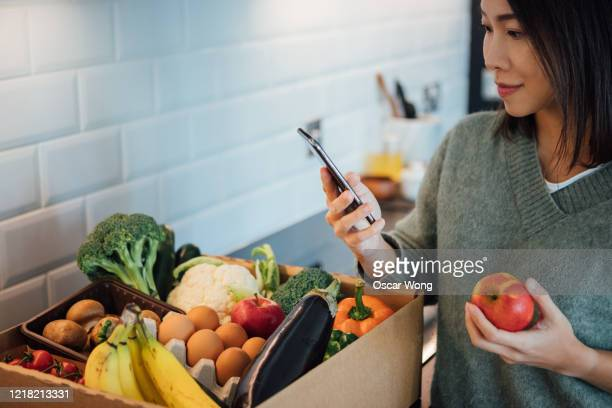 young woman ordering groceries online with smartphone - mobile app stock pictures, royalty-free photos & images