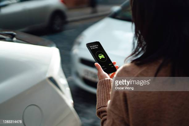 young woman ordering taxi using mobile app on smartphone - looking over shoulder stock pictures, royalty-free photos & images