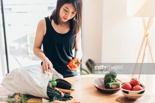 young woman organising groceries after shopping - lifestyles photos stock pictures, royalty-free photos & images