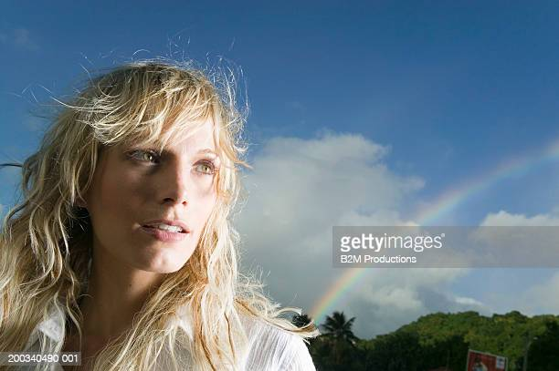 Young woman outdoors, close-up, rainbow in background
