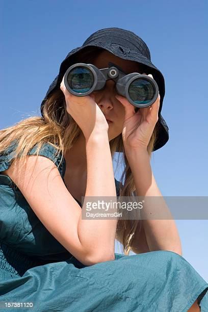 Young Woman Outdoors Facing Camera Looking Through Binoculars