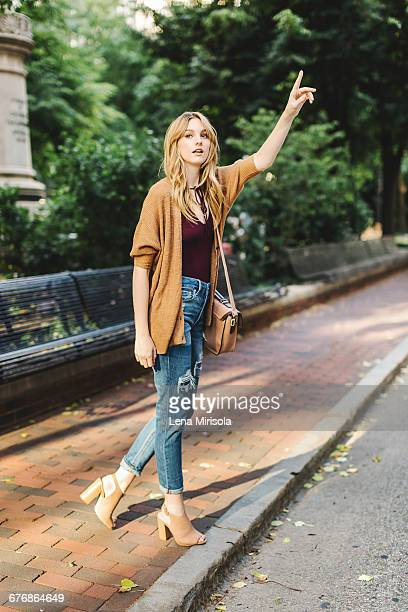 young woman outdoors, hailing taxi - hail stock pictures, royalty-free photos & images