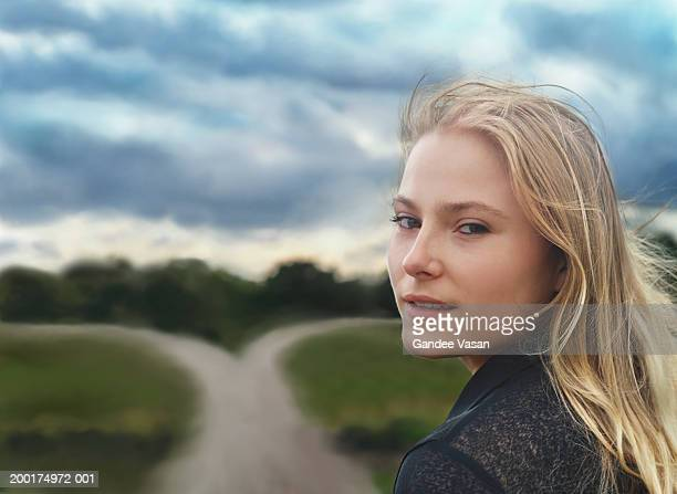Young woman outdoors, looking over shoulder, smiling, portrait