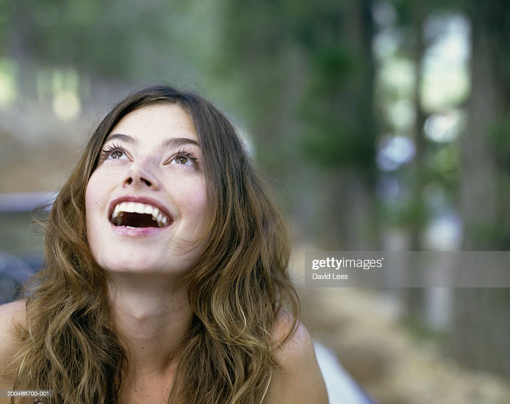 Young woman outdoors, looking up : Stock Photo