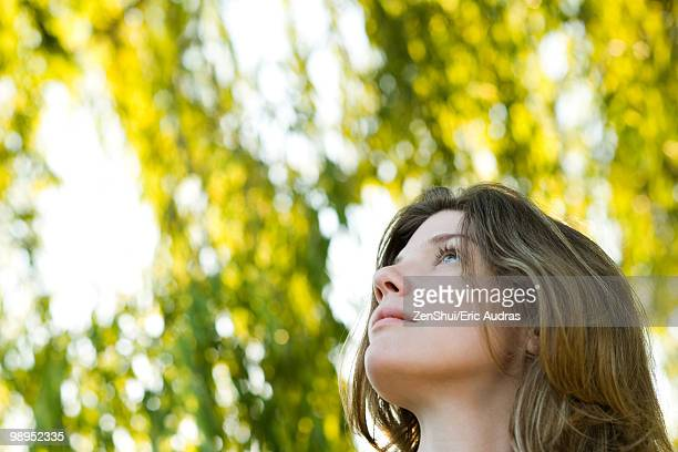 Young woman outdoors, looking up, portrait
