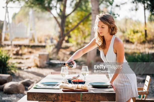young woman, outdoors, preparing dinner table, pouring wine - santa barbara california fotografías e imágenes de stock