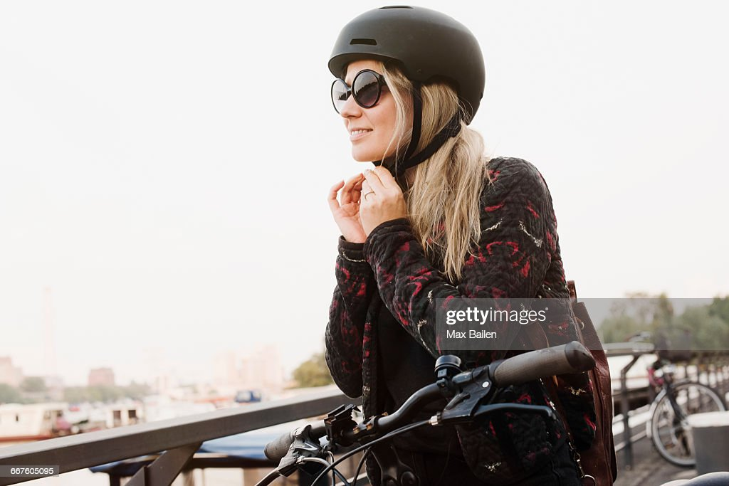 Young woman outdoors, putting on helmet, ready to ride bicycle : Stock Photo